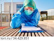 Pflegepersonal vor Klinik beim nachdenklichen Studium von Liste zur... Стоковое фото, фотограф Zoonar.com/Robert Kneschke / age Fotostock / Фотобанк Лори