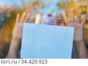 Einsame Seniorin mit Mundschutz hält Zettel an Fenster in Coronavirus... Стоковое фото, фотограф Zoonar.com/Robert Kneschke / age Fotostock / Фотобанк Лори