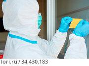 Mitarbeiter bringt gelben Klebenotiz Zettel an Tür oder Fenster von... Стоковое фото, фотограф Zoonar.com/Robert Kneschke / age Fotostock / Фотобанк Лори