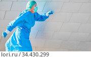 Ärztin in Bereitschaft mit Schutzkleidung eilt zu Notfall wegen Coronavirus... Стоковое фото, фотограф Zoonar.com/Robert Kneschke / age Fotostock / Фотобанк Лори