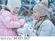 Kind baut mit lachender Mutter einen Schneemann im Winter. Стоковое фото, фотограф Zoonar.com/Robert Kneschke / age Fotostock / Фотобанк Лори