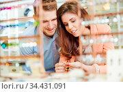 Paar beim Juwelier kauft Armband und anderen Schmuck. Стоковое фото, фотограф Zoonar.com/Robert Kneschke / age Fotostock / Фотобанк Лори