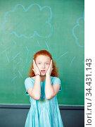 Erschrockenes Mädchen steht vor einer Tafel in der Schule. Стоковое фото, фотограф Zoonar.com/Robert Kneschke / age Fotostock / Фотобанк Лори