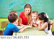 Glückliche Erzieherin und viele Kinder lesen gemeinsam ein Buch in... Стоковое фото, фотограф Zoonar.com/Robert Kneschke / age Fotostock / Фотобанк Лори