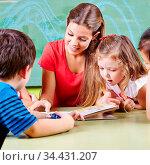 Erzieher im Kindergarten und Kinder lesen zusammen ein Buch. Стоковое фото, фотограф Zoonar.com/Robert Kneschke / age Fotostock / Фотобанк Лори