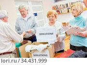 Senioren als freiwillige Helfer sammeln Kleiderspende für Bedürftige... Стоковое фото, фотограф Zoonar.com/Robert Kneschke / age Fotostock / Фотобанк Лори