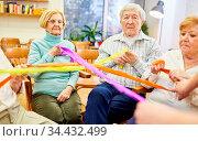 Senioren bei einem Spiel mit bunten Stoffbändern für Gemeinschaft... Стоковое фото, фотограф Zoonar.com/Robert Kneschke / age Fotostock / Фотобанк Лори