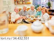 Senioren als Rentner und Freunde trinken zusammen Kaffee im Seniorenheim. Стоковое фото, фотограф Zoonar.com/Robert Kneschke / age Fotostock / Фотобанк Лори