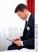 Geschäftsmann im Hotelzimmer arbeitet am Tablet Computer auf dem Bett. Стоковое фото, фотограф Zoonar.com/Robert Kneschke / age Fotostock / Фотобанк Лори