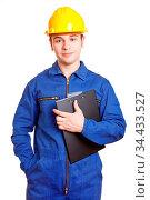 Arbeiter mit Blaumann und Helm hält ein Klemmbrett in der Hand. Стоковое фото, фотограф Zoonar.com/Robert Kneschke / age Fotostock / Фотобанк Лори
