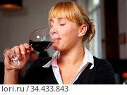 Frau verkostet ein Glas Rotwein in einer Vinothek. Стоковое фото, фотограф Zoonar.com/Robert Kneschke / age Fotostock / Фотобанк Лори