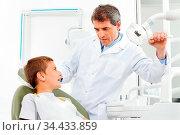 Zahnarzt untersucht einen Jungen in der Zahnarztpraxis. Стоковое фото, фотограф Zoonar.com/Robert Kneschke / age Fotostock / Фотобанк Лори
