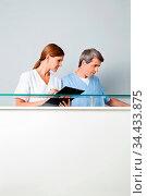 Zwei Ärzte hinter Theke mit Klemmbrett. Стоковое фото, фотограф Zoonar.com/Robert Kneschke / age Fotostock / Фотобанк Лори