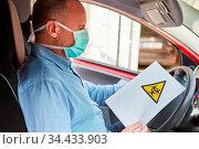 Autofahrer mit Mundschutz und Biogefährdung Warnung auf einem Blatt... Стоковое фото, фотограф Zoonar.com/Robert Kneschke / age Fotostock / Фотобанк Лори