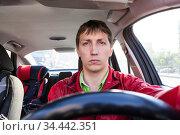 Front view at male driver sitting close to steering wheel in car, man driving a vehicle. Стоковое фото, фотограф Кекяляйнен Андрей / Фотобанк Лори