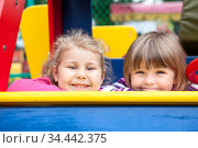 Two cheerful little girls laughing while sitting in frame of children playground, foxlike behaviour. Стоковое фото, фотограф Кекяляйнен Андрей / Фотобанк Лори