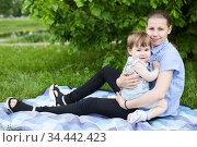 Portrait of young girl embracing her infant sister, girls sitting on blanket on green grass in park. Стоковое фото, фотограф Кекяляйнен Андрей / Фотобанк Лори