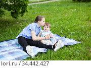 Teen age girl kissing her toddler sister while sitting on blanket in green grass on picnic, summer meadow. Стоковое фото, фотограф Кекяляйнен Андрей / Фотобанк Лори