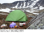 Food cooking on portable gas stove during hiking, small green tent is in mountain valley for resting, mountains with severe weather and snow patches. Стоковое фото, фотограф Кекяляйнен Андрей / Фотобанк Лори