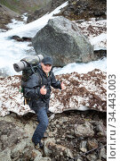 Adult backpacker showing thumbs up while hiking along mountain river with melting snow bed, mountaineering with backpack. Стоковое фото, фотограф Кекяляйнен Андрей / Фотобанк Лори