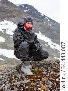 Portrait of Caucasian teenage boy dressing warm hiking outfit for mountaineering, young man sitting on big stone in mountains. Стоковое фото, фотограф Кекяляйнен Андрей / Фотобанк Лори