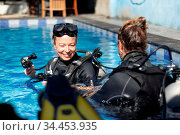 Female diving instructor teaches student to scuba dive in swimming... Стоковое фото, фотограф Zoonar.com/Matej Kastelic / easy Fotostock / Фотобанк Лори