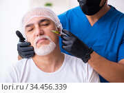 Old man visiting male doctor for plastic surgery. Стоковое фото, фотограф Elnur / Фотобанк Лори