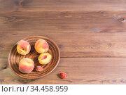 Несколько свежих спелых персиков в терракотовой тарелке на деревянном столе. Стоковое фото, фотограф Наталья Гармашева / Фотобанк Лори