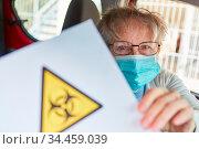 Warnung vor Biogefährdung wegen Covid-19 und Coronavirus Epidemie. Стоковое фото, фотограф Zoonar.com/Robert Kneschke / age Fotostock / Фотобанк Лори