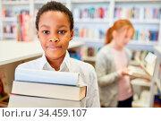 Afrikanischer Schüler in Grundschüle trägt Bücher aus der Bibliothek. Стоковое фото, фотограф Zoonar.com/Robert Kneschke / age Fotostock / Фотобанк Лори