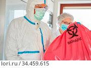 Reinigungskräfte in Schutzkleidung entsorgen kontaminierten Abfall... Стоковое фото, фотограф Zoonar.com/Robert Kneschke / age Fotostock / Фотобанк Лори