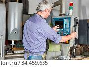 Arbeiter in Metallfabrik bedient den Touchscreen einer CNC Fräsmaschine. Стоковое фото, фотограф Zoonar.com/Robert Kneschke / age Fotostock / Фотобанк Лори