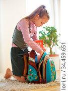 Kind packt zu Hause den Schulranzen für die Schule. Стоковое фото, фотограф Zoonar.com/Robert Kneschke / age Fotostock / Фотобанк Лори