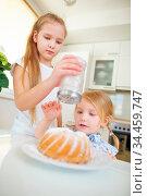Zwei Kinder backen einen Kuchen in der Küche und dekorieren ihn mit... Стоковое фото, фотограф Zoonar.com/Robert Kneschke / age Fotostock / Фотобанк Лори