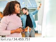 Afrikanerin als Studentin oder Azubi mit Schere und Klebeband vor... Стоковое фото, фотограф Zoonar.com/Robert Kneschke / age Fotostock / Фотобанк Лори