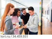 Kollegen im Start-Up Team haben Spaß und lachen über SMS auf dem ... Стоковое фото, фотограф Zoonar.com/Robert Kneschke / age Fotostock / Фотобанк Лори