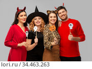 friends in halloween costumes with party props. Стоковое фото, фотограф Syda Productions / Фотобанк Лори