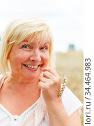 Alte lächelnde Frau im Weizenfeld mit einer Ähre im Mund. Стоковое фото, фотограф Zoonar.com/Robert Kneschke / age Fotostock / Фотобанк Лори