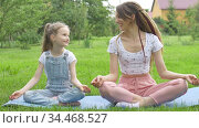 Young mother with dreadlocks and little daughter are doing yoga exercises in lotus position on grass in the park at the day time. Concept of friendly family and of summer vacation. Стоковое видео, видеограф Ольга Балынская / Фотобанк Лори