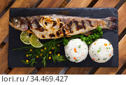 Deliciously baked whole trout with rice, served with lemon and greens. Стоковое фото, фотограф Яков Филимонов / Фотобанк Лори