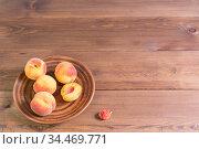 Несколько свежих спелых персиков в коричневой тарелке на деревянном столе.  Свободное место для текста. Стоковое фото, фотограф Наталья Гармашева / Фотобанк Лори