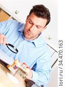 Mann im Büro liest eine Akte aufmerksam mit einer Lupe. Стоковое фото, фотограф Zoonar.com/Robert Kneschke / age Fotostock / Фотобанк Лори