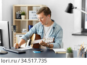 man with guitar writing to music book at home. Стоковое фото, фотограф Syda Productions / Фотобанк Лори