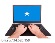 Hands working on laptop showing on the screen the flag of Somalia. Стоковое фото, фотограф Zoonar.com/Micha Klootwijk / age Fotostock / Фотобанк Лори