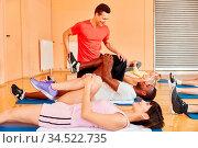 Fitnesstrainer zeigt Übung im Kurs im Fitnesscenter. Стоковое фото, фотограф Zoonar.com/Robert Kneschke / age Fotostock / Фотобанк Лори