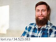Lächelnder junger Hipster Mann mit Vollbart als Arbeiter oder Handwerker. Стоковое фото, фотограф Zoonar.com/Robert Kneschke / age Fotostock / Фотобанк Лори