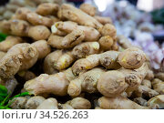 Fresh ginger root on showcase of greengrocery shop for sale to customers. Стоковое фото, фотограф Яков Филимонов / Фотобанк Лори