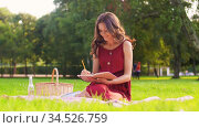 happy woman with diary and picnic basket at park. Стоковое видео, видеограф Syda Productions / Фотобанк Лори
