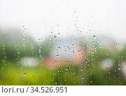 Капли дождя на стекле окна. Дачные дома на заднем плане. Стоковое фото, фотограф E. O. / Фотобанк Лори