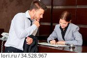 Frau am Empfang vom Hotel gibt einem Gast Tipps auf einem Stadtplan. Стоковое фото, фотограф Zoonar.com/Robert Kneschke / age Fotostock / Фотобанк Лори